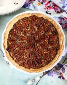 Overhead shot of chocolate pecan pie in a white dish on a blue background.
