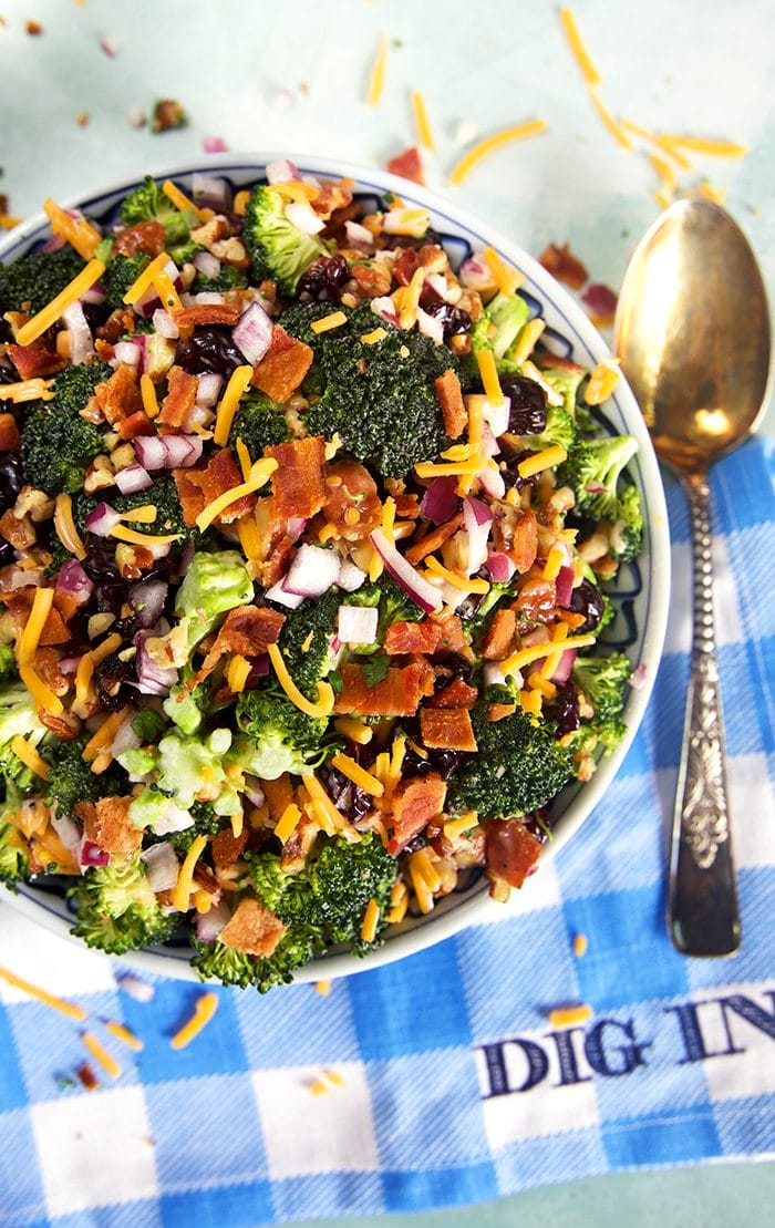 Overhead shot of broccoli salad with bacon on a blue and white checked napkin that says Dig In.