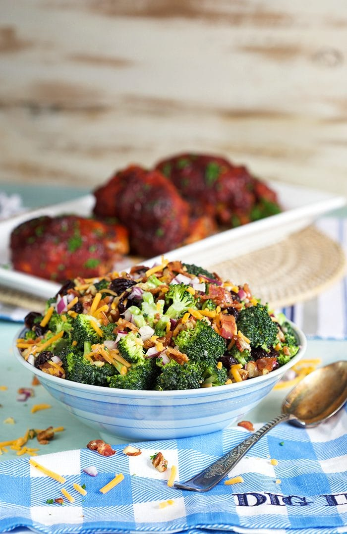 Broccoli Salad with Bacon in a blue and white bowl with chicken on a white platter.