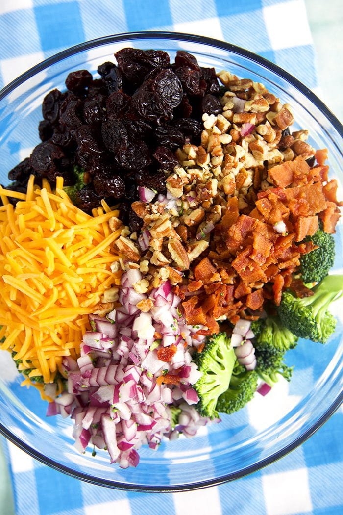 Overhead shot of ingredients for broccoli salad in a glass bowl.