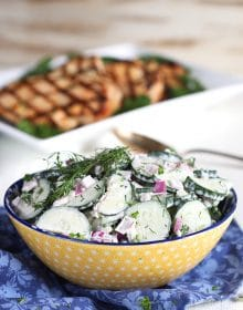 Creamy Cucumber Salad with red onion and dill in a yellow bowl on a blue napkin.