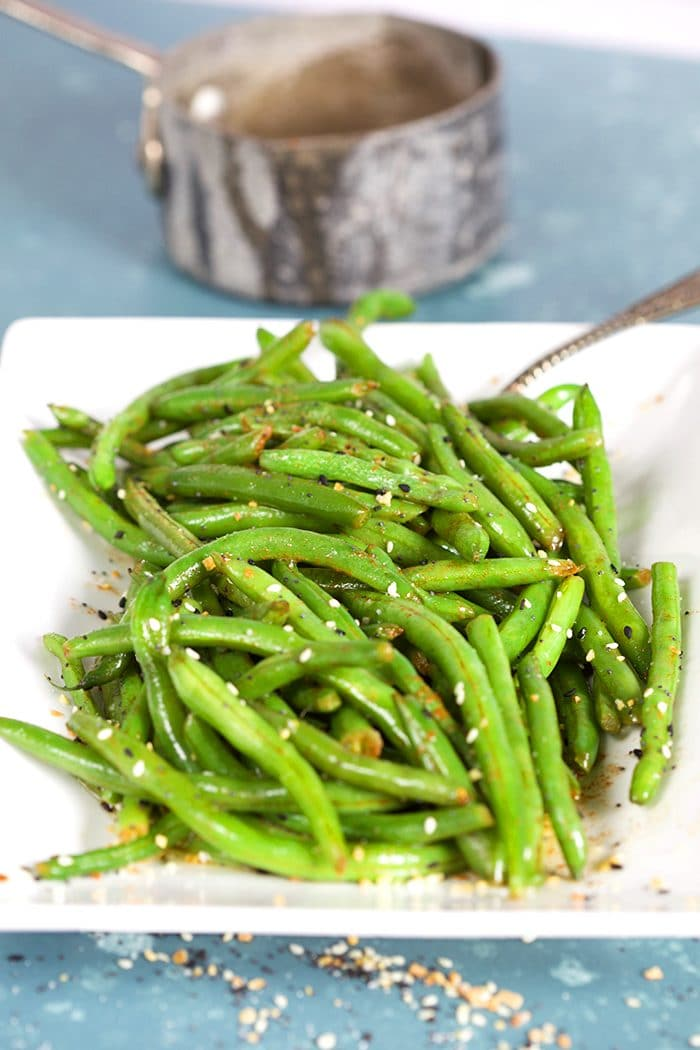 Green beans on a white platter on a blue background.