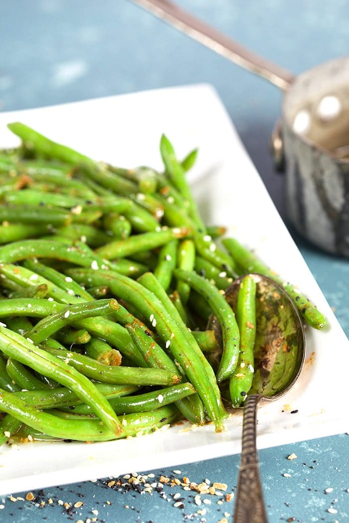 Green beans on a white platter with a silver spoon.