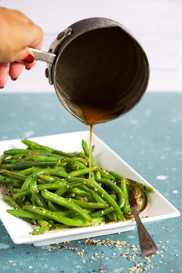 Sauteed green beans on a white platter with brown butter being poured over them.
