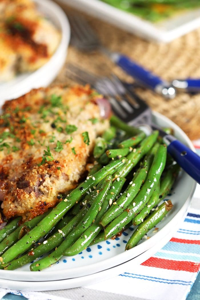 Sauteed green beans on a white plate with a breaded pork chop.