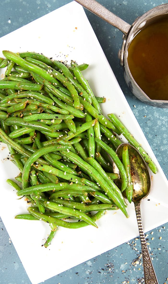 Overhead shot of green beans on a white platter with a silver spoon.