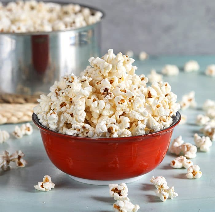 Stovetop popcorn in a red bowl on a blue background.