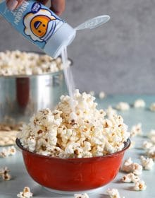 Popcorn in a red bowl with popcorn salt being put on top.