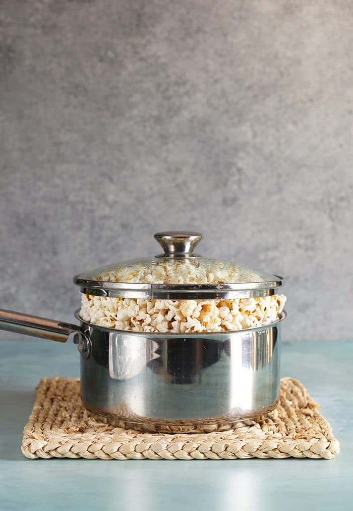 Stovetop popcorn in a stainless steel pot with a glass lid.