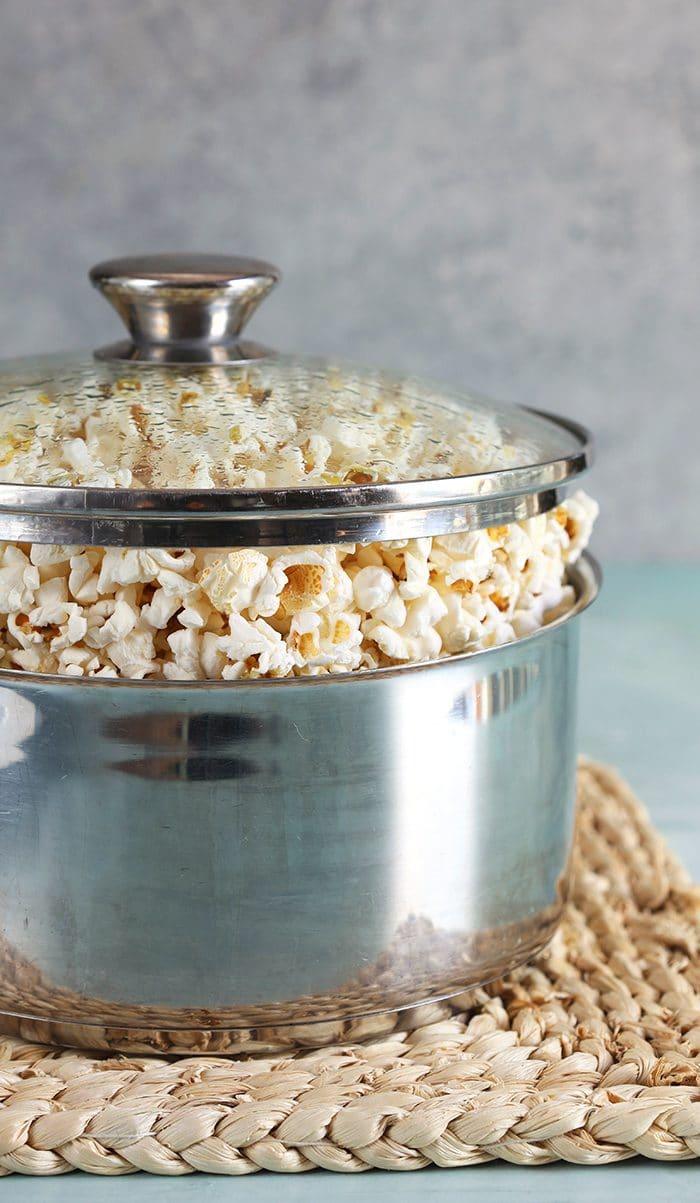 Closeup of popcorn in a pot with a glass lid.