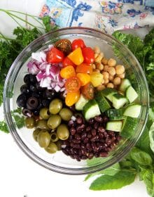 overhead shot of ingredients for chickpea salad in a glass bowl with herbs.