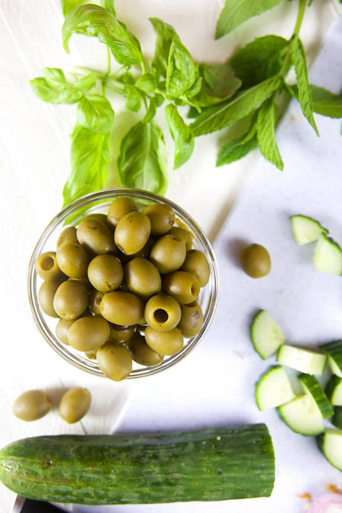 Bowl of green olives with chopped cucumber and herbs.