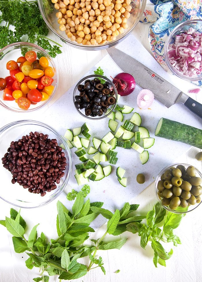 Overhead shot of ingredients for chickpea salad on a white background with a knife.