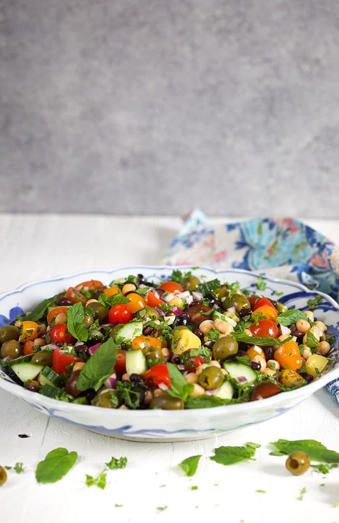 Bowl of chickpea salad on a white background.