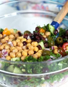 Ingredients for chickpea salad in a glass bowl with a spatula.