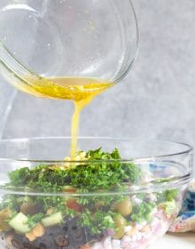 dressing being poured over chickpea salad in a glass bowl.