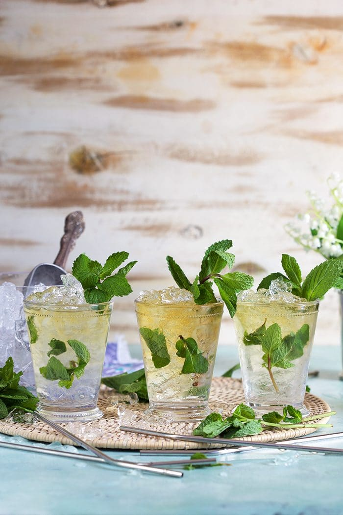 Three mint juleps in a row on a blue background.