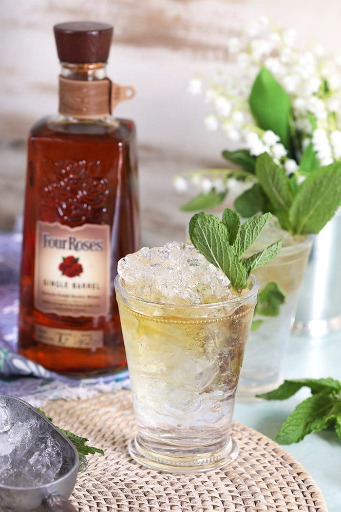 Mint Julep in a glass julep cup with a bottle of Four Roses Bourbon in the background.