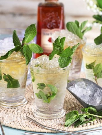 Four mint juleps in glass julep cups with an ice scoop.