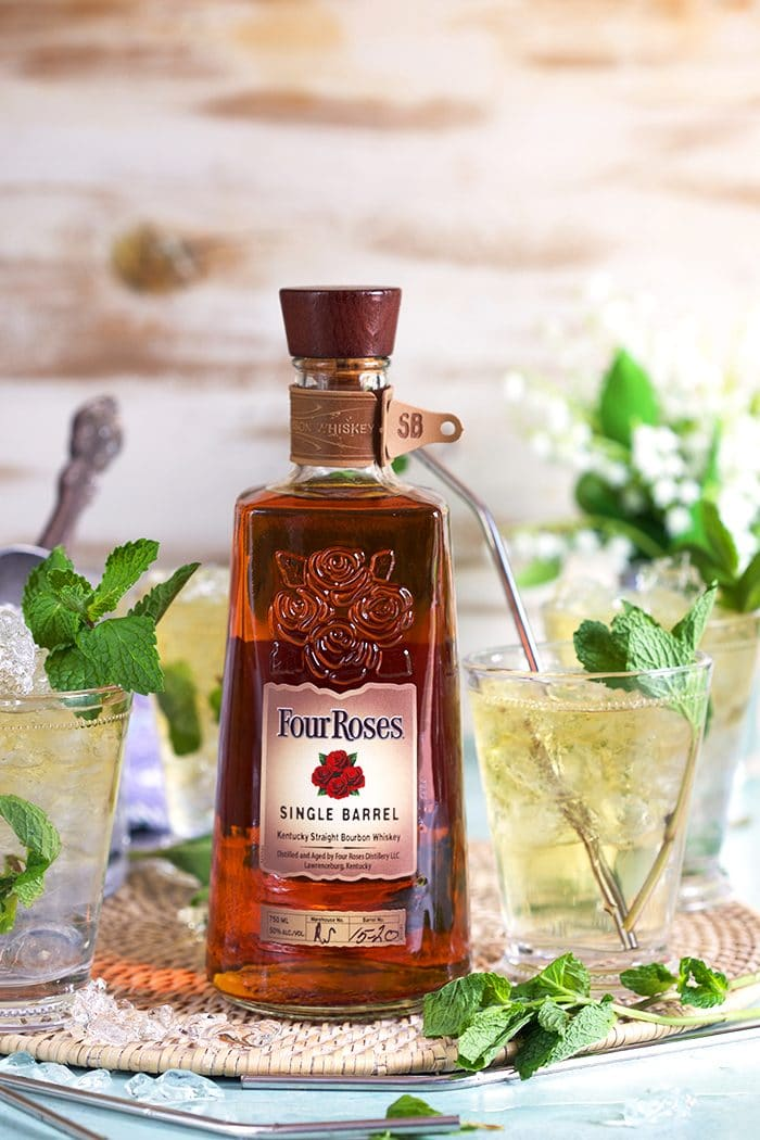 Four Roses Bourbon bottle with Mint Juleps in glass julep cups.