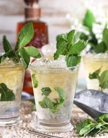 Mint julep cocktail in a glass julep cup with mint and crushed ice.