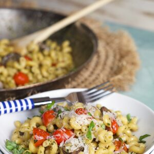 Pesto Cavatappi on a white bowl with a blue background and blue and white striped fork.