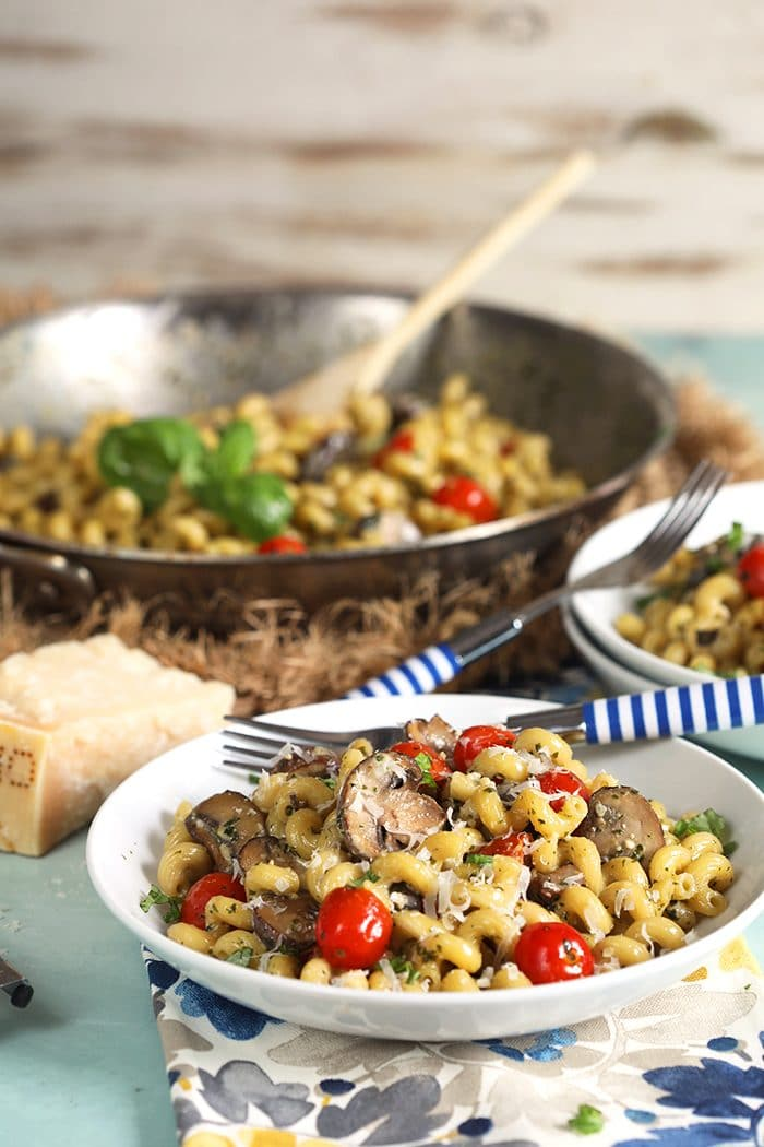 Pesto Cavatappi being served from a skillet into a white bowl.