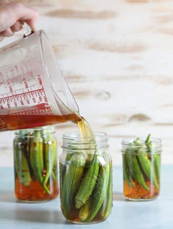 Okra in canning jars with a measuring cup pouring brine into the jars.