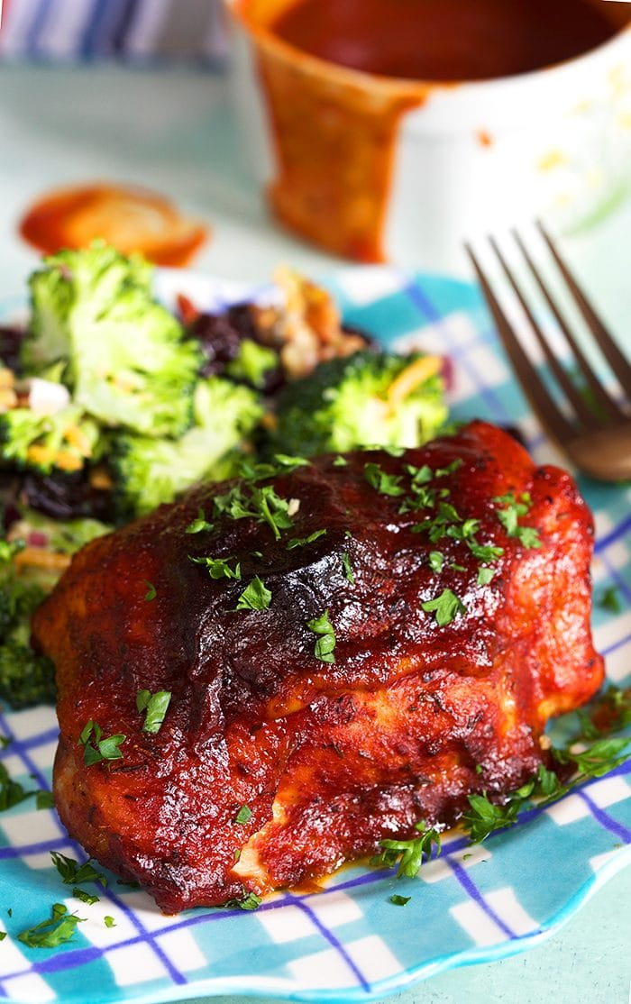 BBQ Chicken thigh on a plaid plate with broccoli salad.
