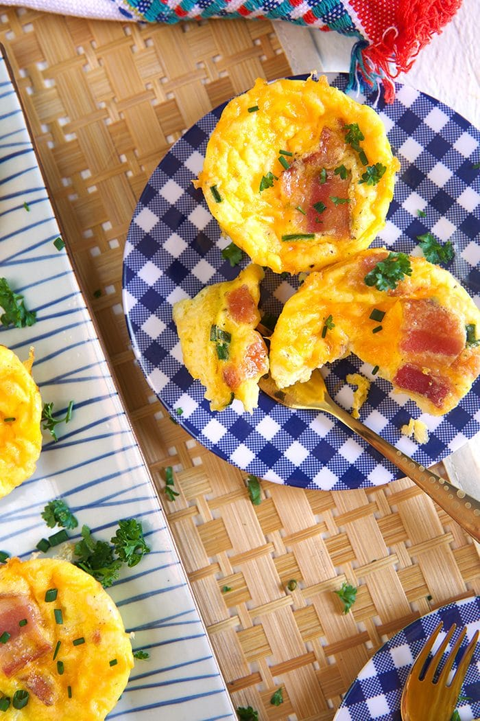 Overhead shot or two bacon egg muffins on a blue and white plate.