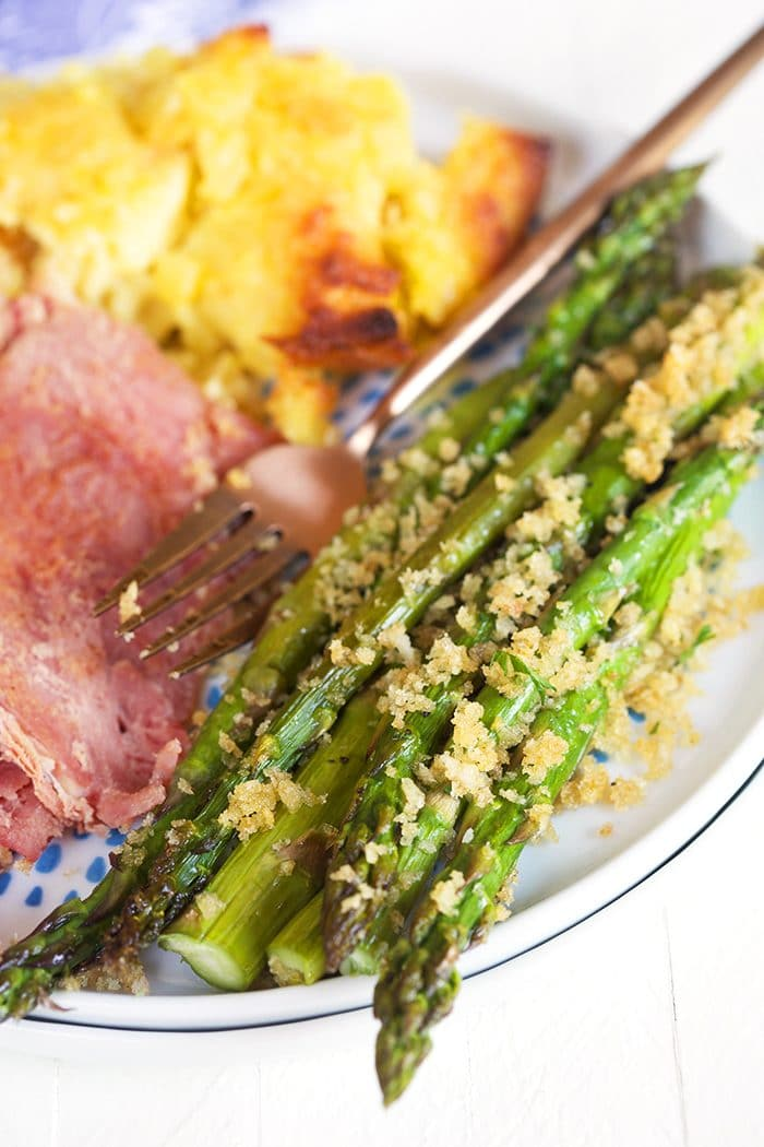 Asparagus with panko on a white plate with ham and pineapple casserole.