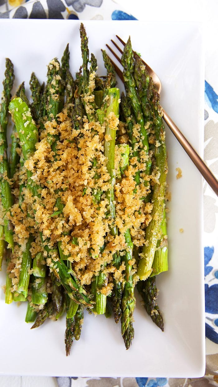 Overhead shot of baked asparagus on a white platter with a crispy panko crust.