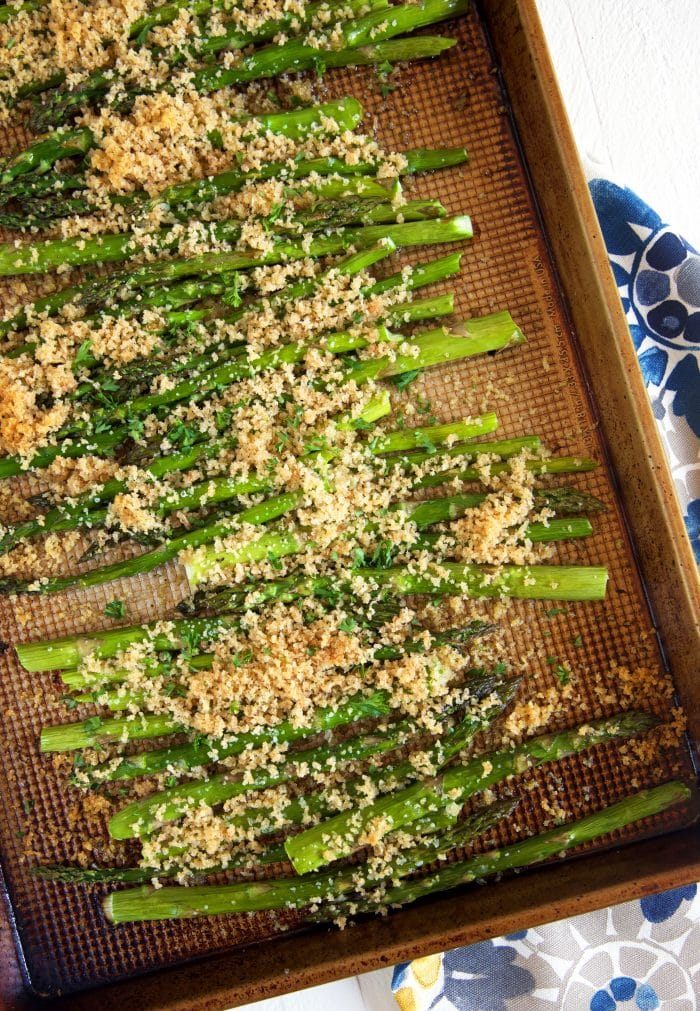 Overhead shot of baked asparagus on a baking sheet with crispy panko topping.