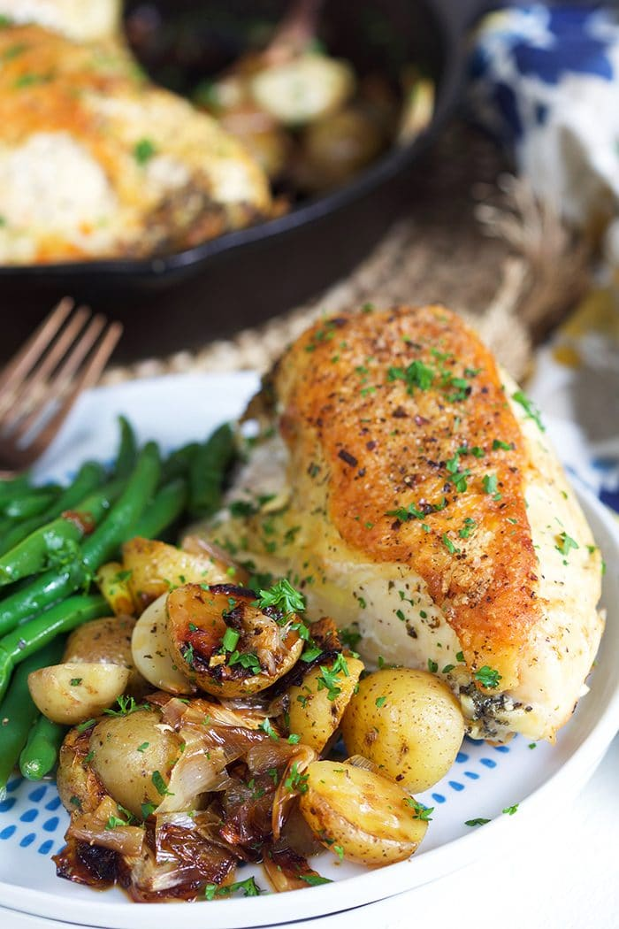 Crispy skinned cast iron skillet chicken with potatoes on a white plate.