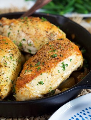 Cast Iron skillet chicken breasts in a cast iron skillet with a blue plate in the front.