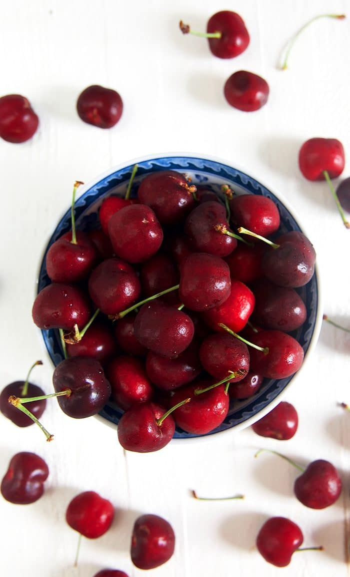 Bowl of cherries on a white background.