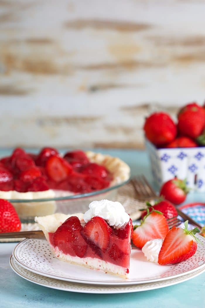 Strawberry pie on a white plate with whipped cream and berries in the background.