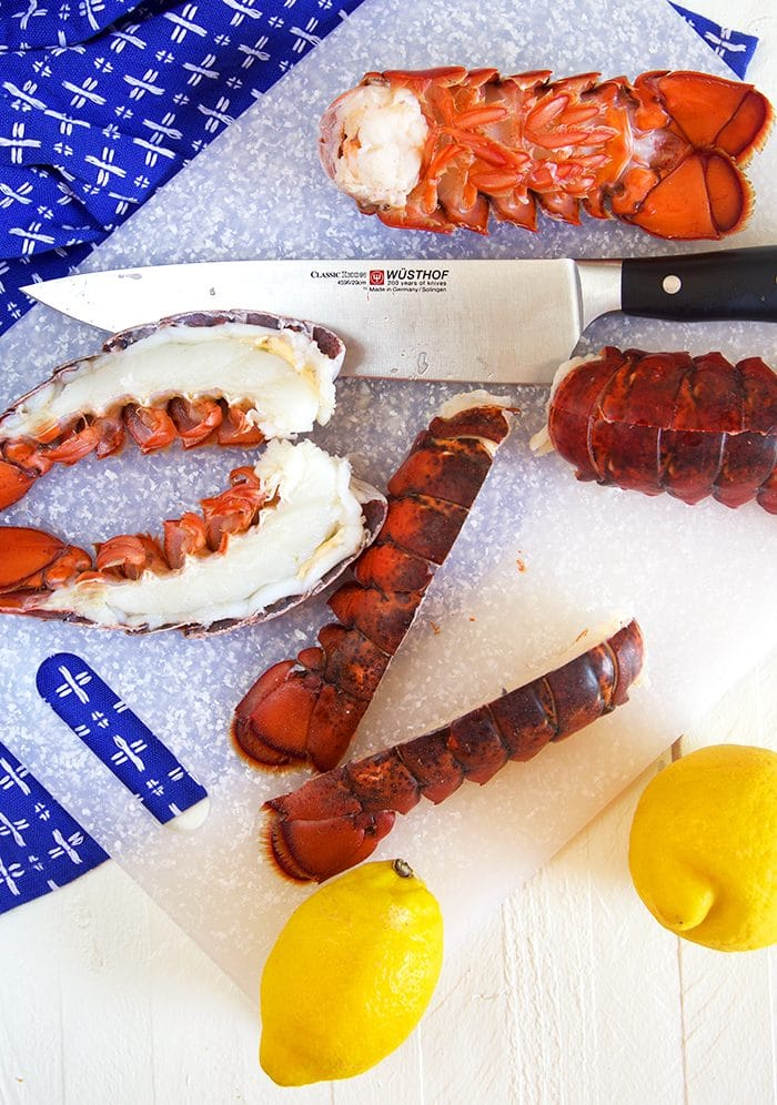 Lobster tails on a cutting board being split with a knife.