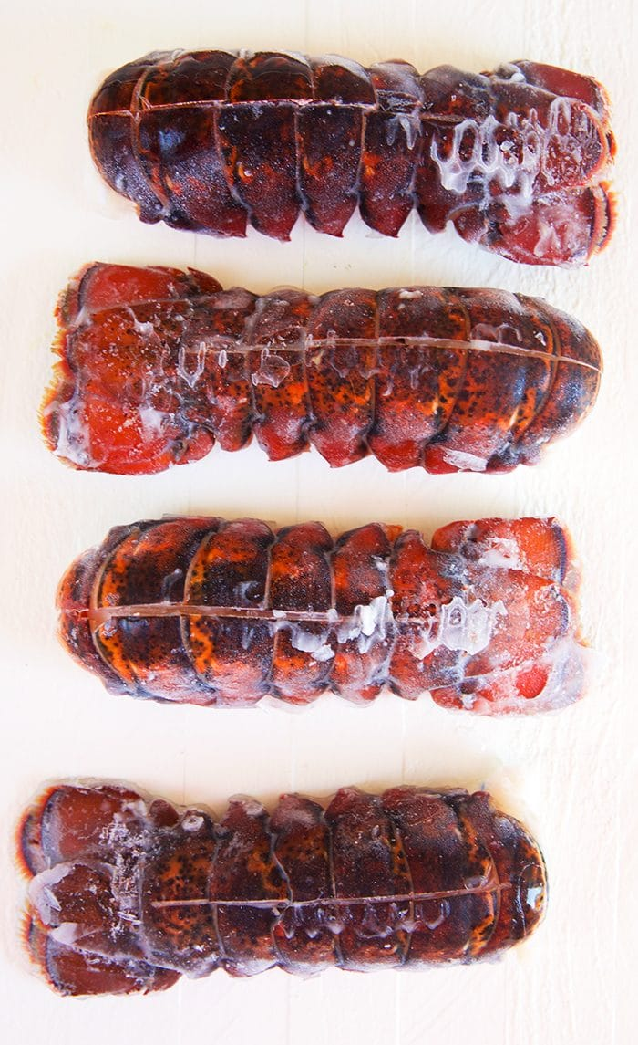 Frozen lobster tails on a white background.