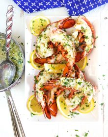 Garlic butter sauce in a saucepan next to a plate of grilled lobster tails.
