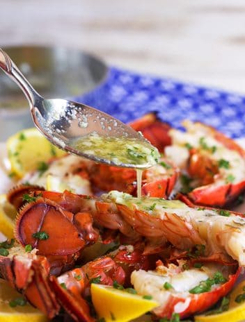 Grilled Lobster Tails with butter sauce being drizzled overtop.