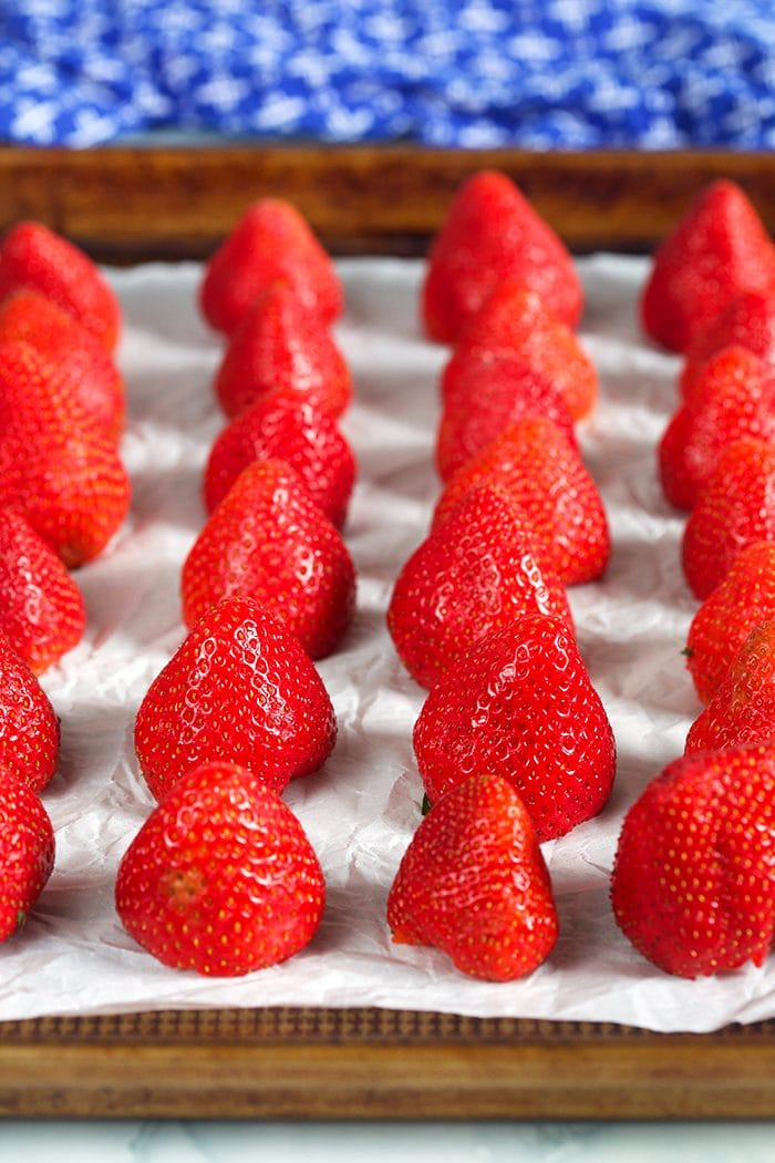 Fresh strawberries arranged on a baking sheet for freezing.