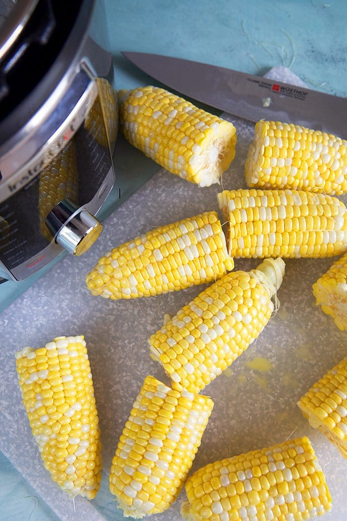 Overhead shot of corn on the cob cut in half in front of an Instant Pot.