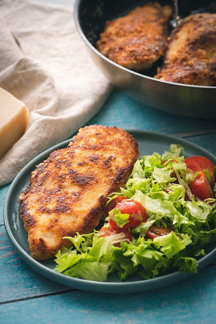 Parmesan CRusted Chicken Cutlet on a plate with a green salad on a blue background.