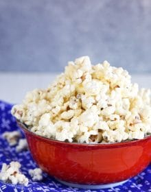 White cheddar popcorn in a red bowl on a blue napkin.