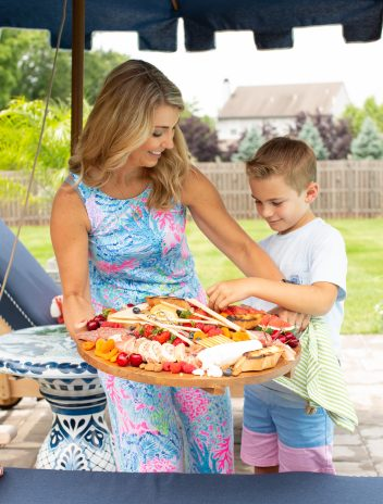 Mom and boy serving a summer charcuterie board outside by a pool.