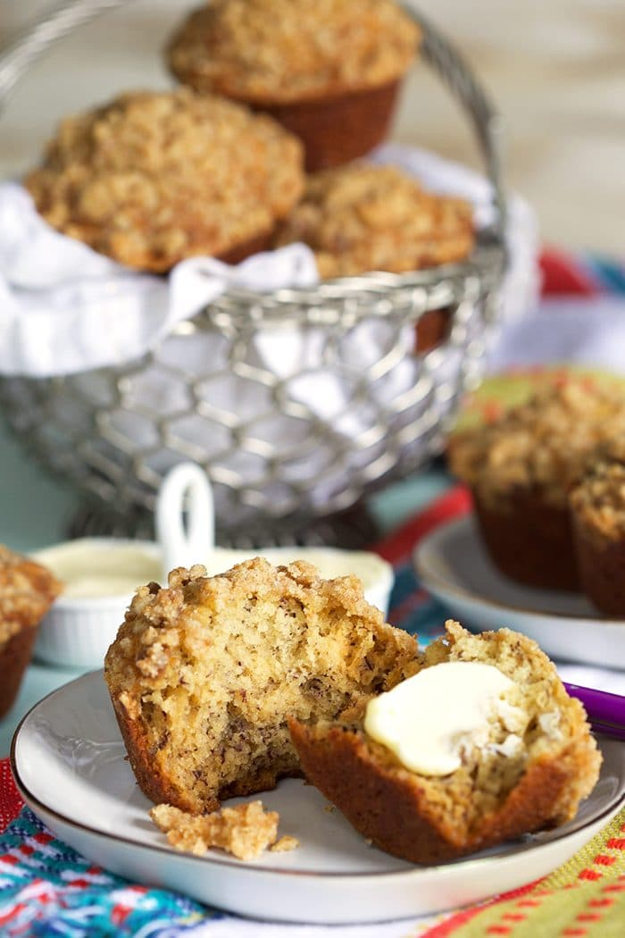 Banana Bread muffin on a white plate with a pat of butter.