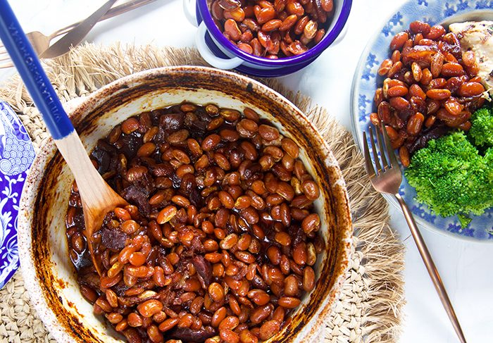 overhead shot of baked beans in a blue and white pot with a blue wooden spoon.