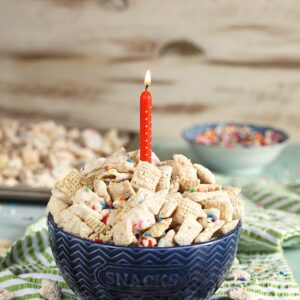 blue bowl with birthday cake puppy chow and a candle.