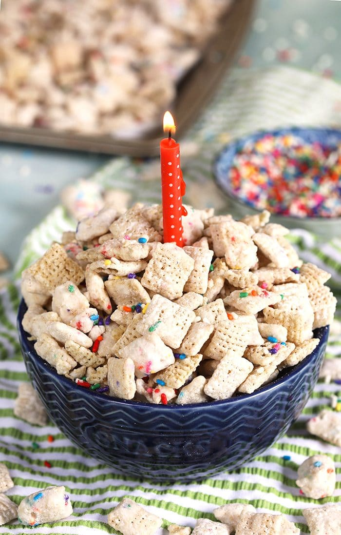 Birthday Cake Puppy Chow in a blue bowl with a pink candle